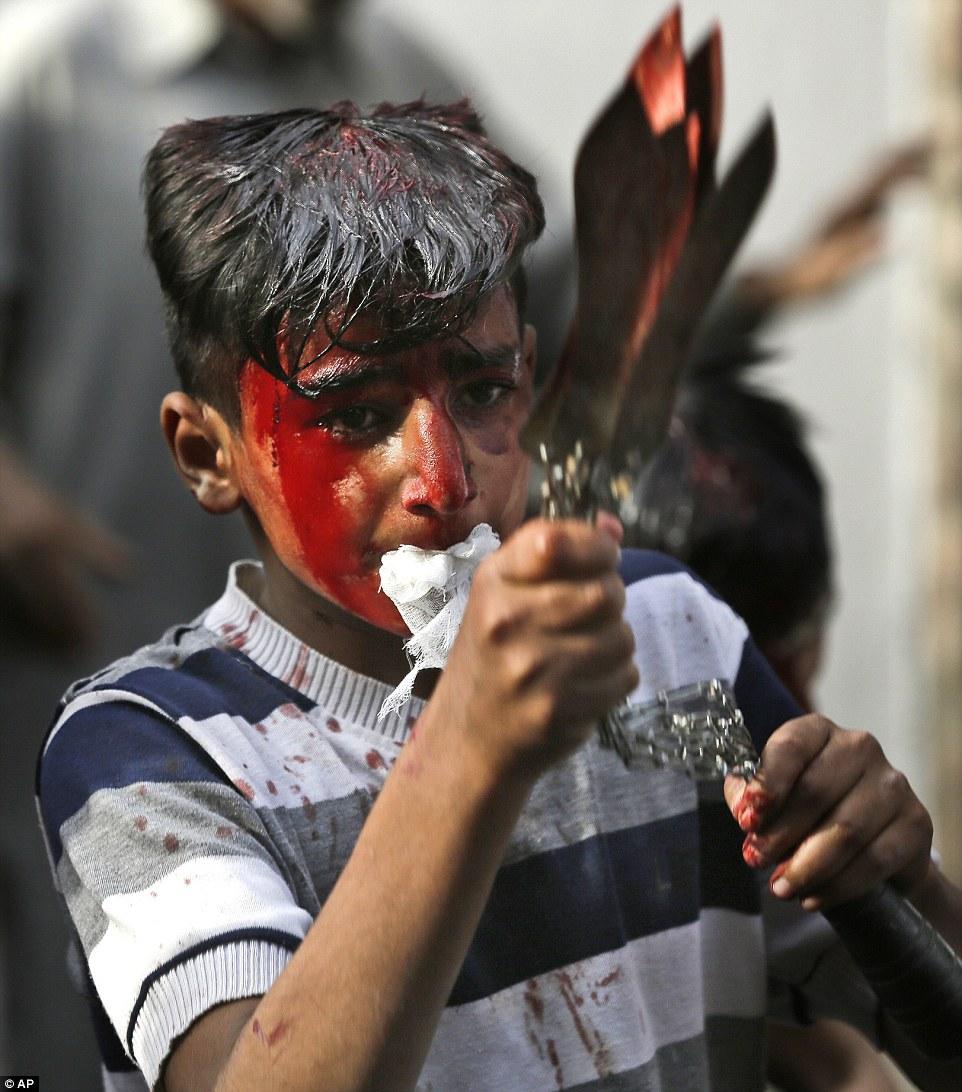 A Kashmiri Shiite Muslim boy flagellates himself during a Muharram procession in Srinagar in Indian controlled Kashmir