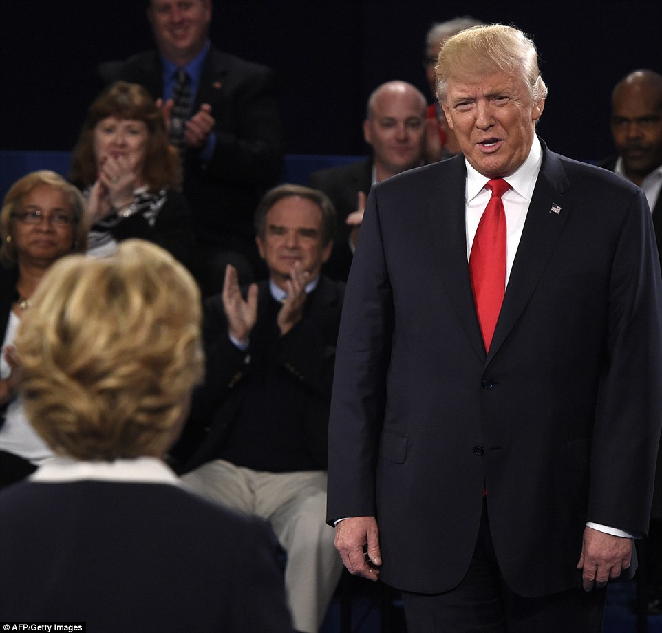 Hillary Clinton and Donald Clinton appear on the debate stage as the audience claps during the town hall event on Sunday night