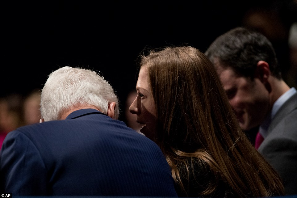 Former President Bill Clinton (left) speaks to his daughter Chelsea Clinton (center) and her husband Marc Mezvinsky (right)