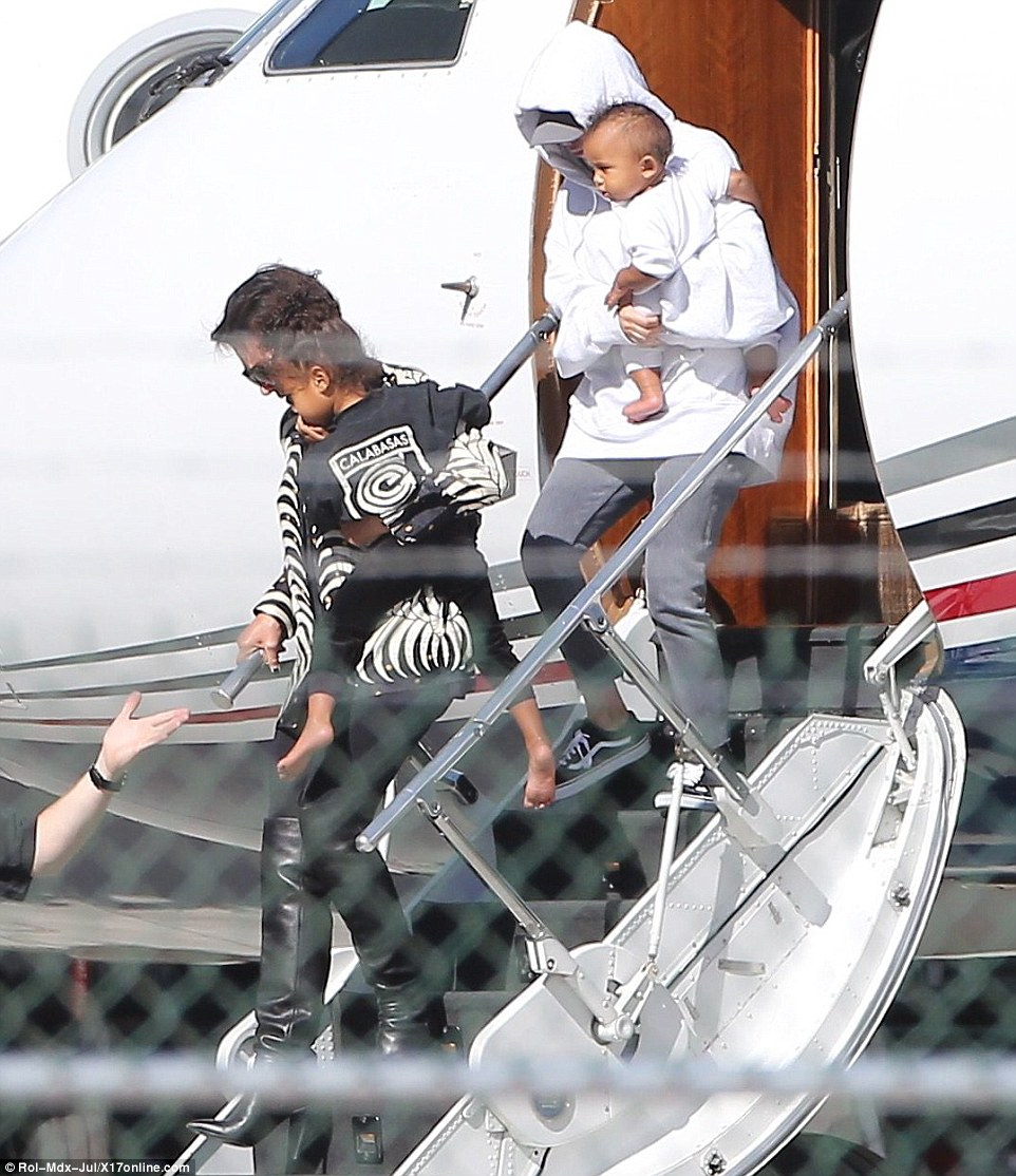 Fear: Kim's ordeal began at 2:35am when three men dressed in police uniforms appeared at the glass doors at the building's entrance and then handcuffed security guard Abdulrahman. Pictured: Kim lands in the US on her private jet after giving a statement to French police