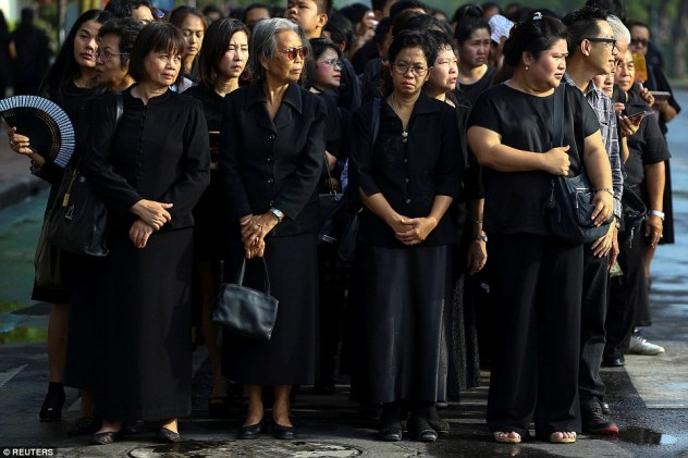 People wear black as they stand in line to offer condolences for Thailand's late King Bhumibol Adulyadej at the Grand Palace in Bangkok