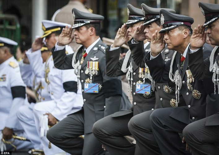 Police and military personnels salute as a convoy of vehicles carrying body of the late King Bhumibol Adulyadej moves toward the Grand Palace in Bangkok