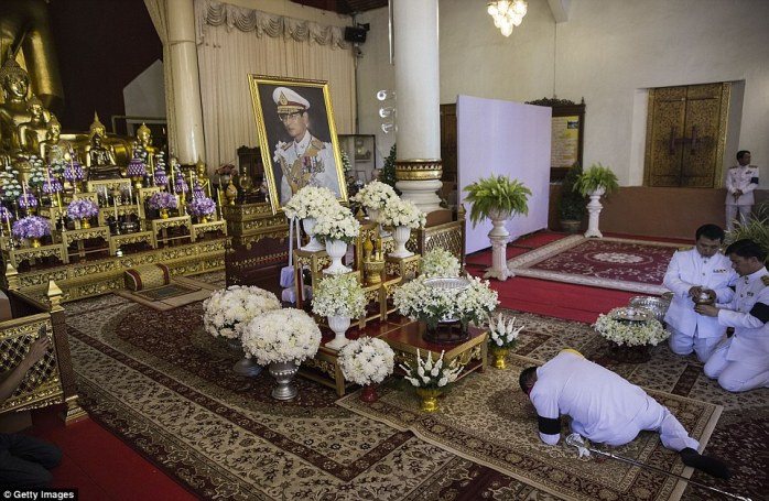 A uniformed official prostrates himself in front of a picture of the King during a ceremony at Wat Phra Singh on October 14