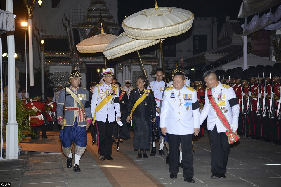 Thai Crown Prince Vajiralongkorn, (second left) the late king's son, and Princess Sirindhorn (right) arrive at Grand Palace before presiding over a Buddhist funeral rite at a hall inside the Grand Palace