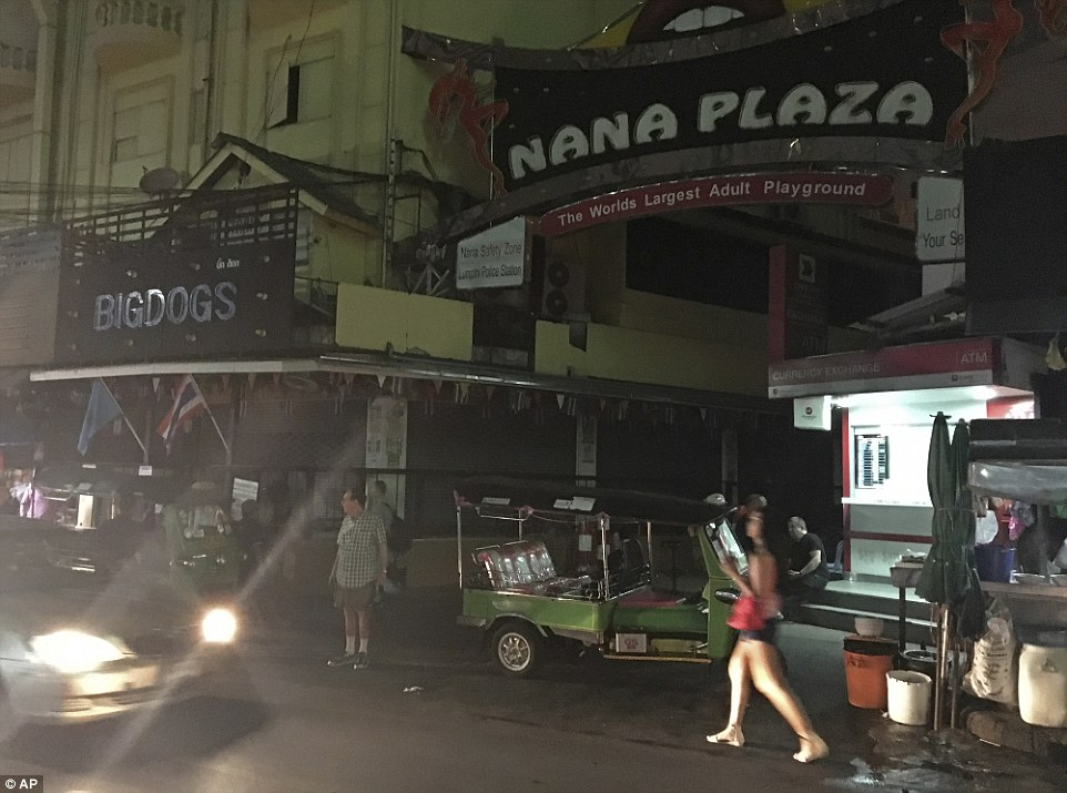 People walk past Bangkokís Nana Plaza red-light district, after it closed down temporarily following the death Thursday of Thailandís 88-year-old King Bhumibol Adulyadej, who was the world's longest reigning monarch
