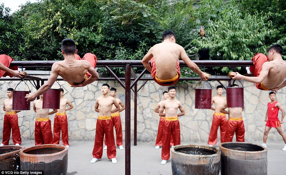 The students display their incredible core strength as they pull water from a well while hanging upside down from bars