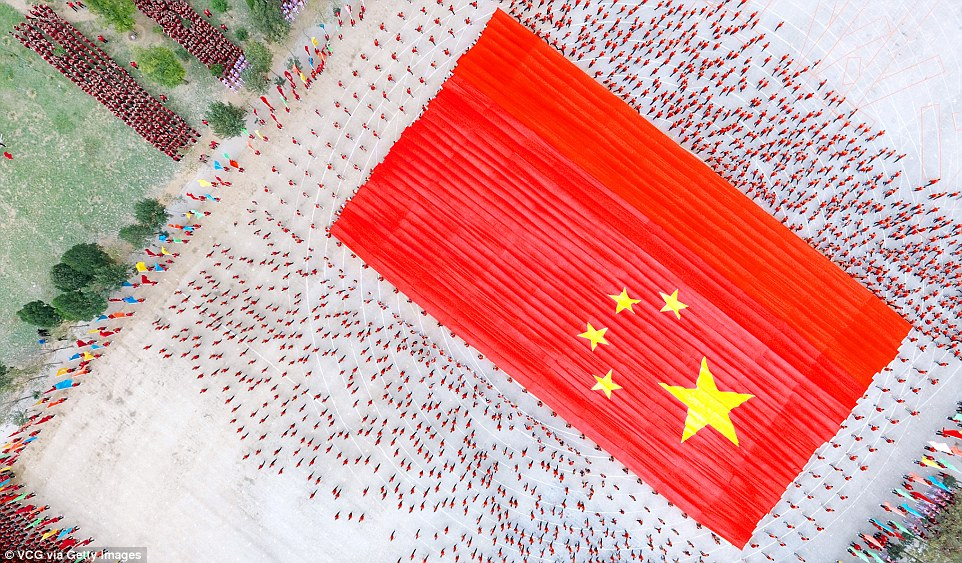 The competitors hold up a huge Chinese flag, during the rehearsal days of the festival, as others crowd around