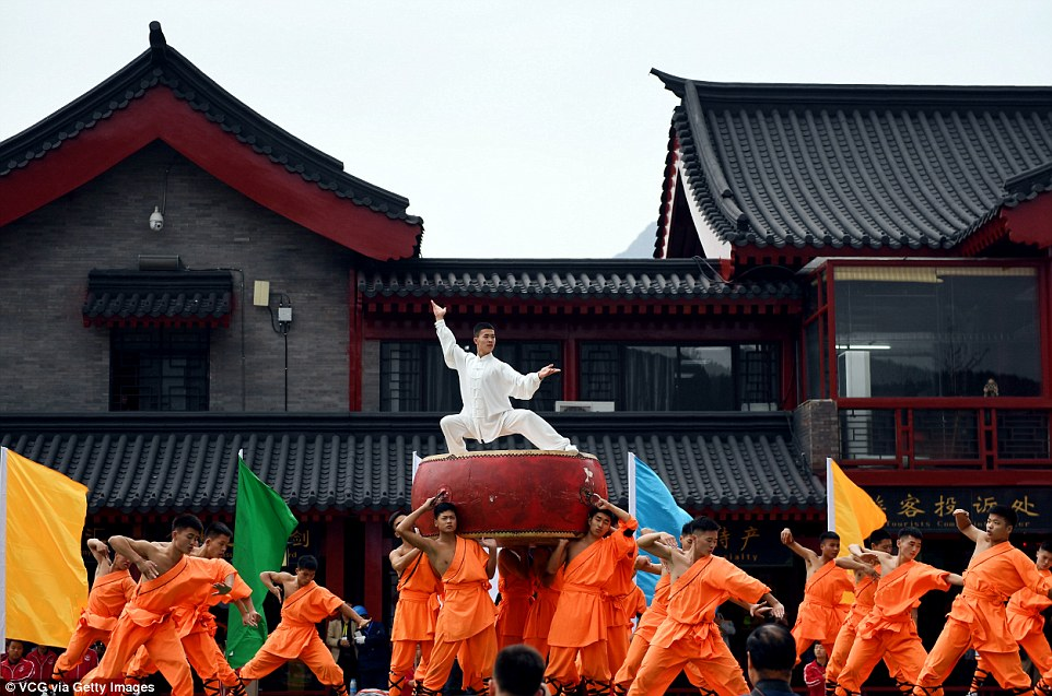 A group of men in orange costume hold up one man in white, in something akin to a Saturday Night Fever pose during the rehearsals