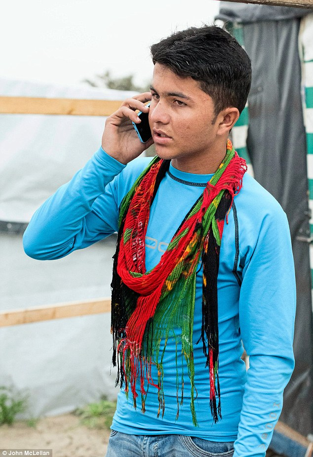 Shamsher Sherin, aged 13 pictured having a brief telephone conversation with his father Hazrat Gul Sherin in Birmingham. He has never heard of Lily Allen
