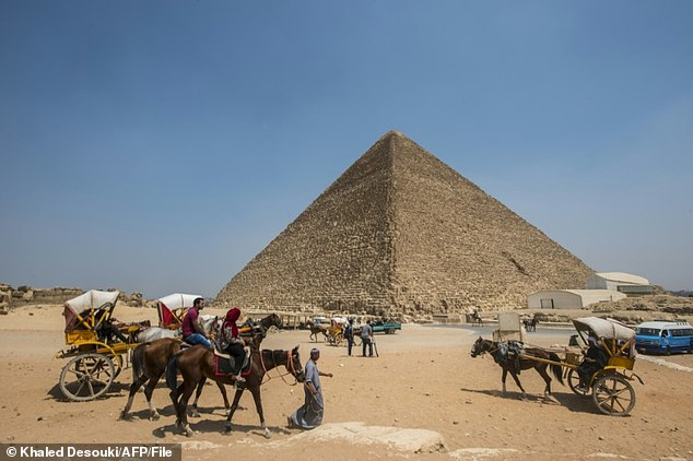 Egyptians ride their carts past the Great Pyramid of Cheops, aka Pyramid of Khufu or the Great Pyramid of Giza. Two previously unknown cavities have been uncovered inside the structure