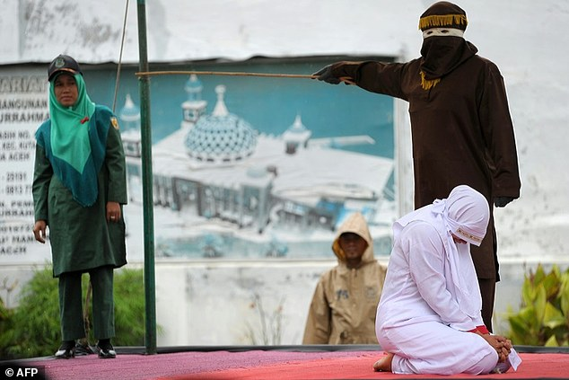 A Muslim woman is caned in Banda Aceh, Indonesia, for breaking sharia law