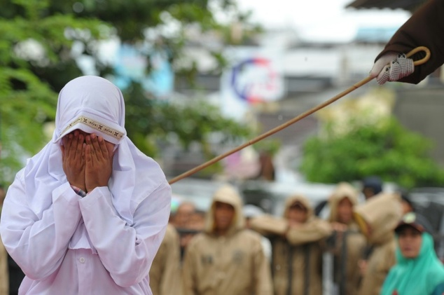 A Muslim woman is caned in Banda Aceh, Indonesia, on October 17, after she was found guilty of breaking sharia law - pertaining to bans on intimacy between unmarried people