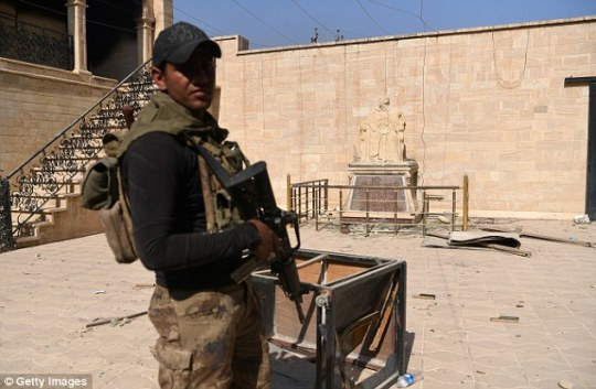 An Iraqi soldier stands guard next to a church in Bartella. In the background is a statue of Christ with its head broken off.