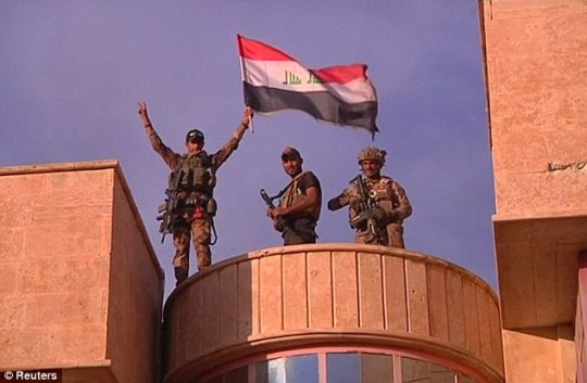 Iraqi troop wave the Iraqi flag after liberating the predominantly Christian town of Bartella