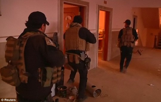 Iraqi forces enter a church in the town of Bartella in a bid to liberate it from ISIS control