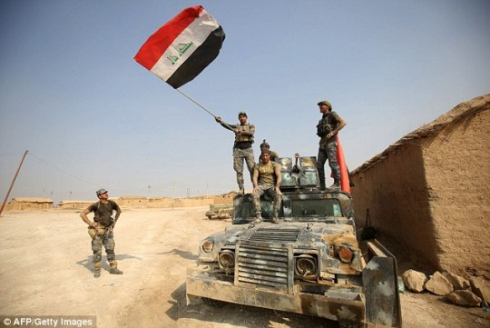 Iraqi government forces raise their national flag as they enter the village of al-Khuwayn, south of Mosul