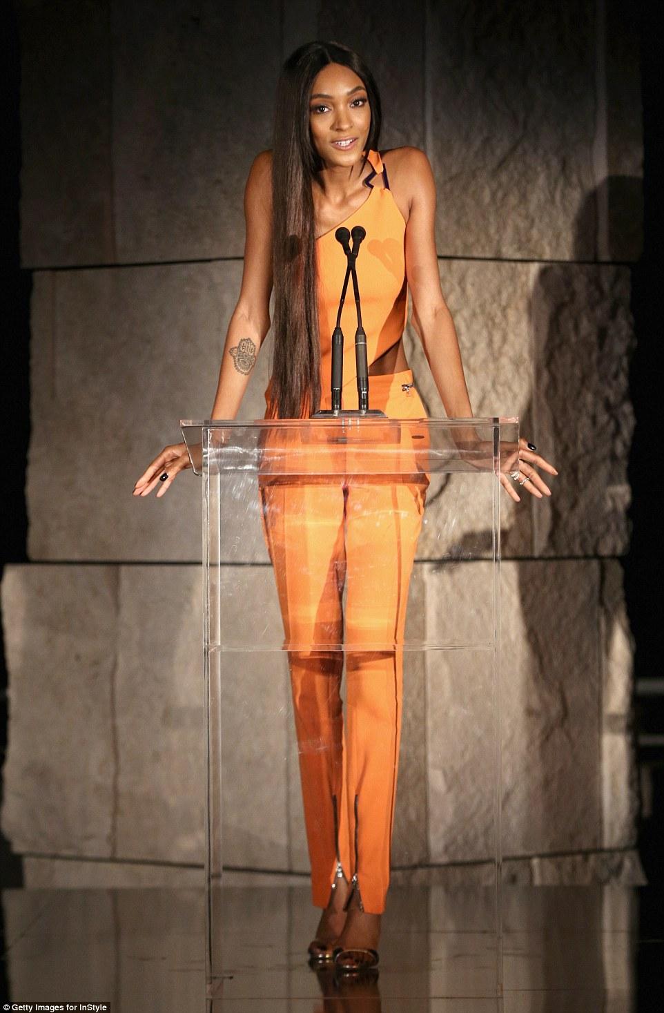 Tomando o estágio: O modelo elegante subiu ao palco no seu conjunto laranja atraente