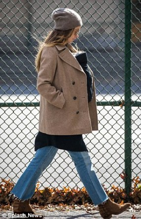 Yummy mummy: Looking effortlessly chic, she teamed the garment with vintage style jeans and brown cowboy boots, whilst she added some glamour with a pair of reflective gold shades