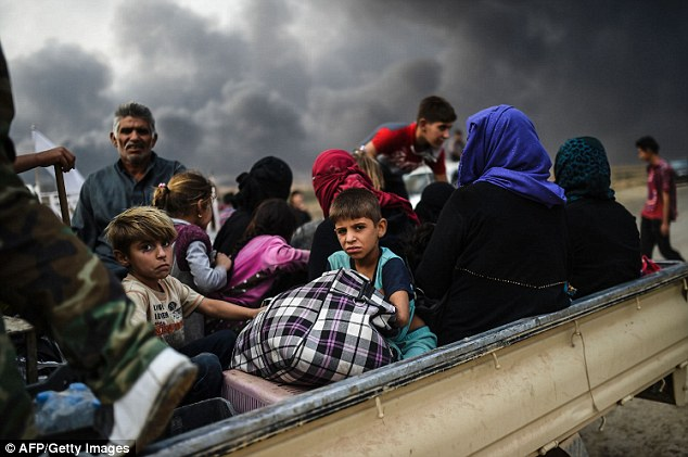 Iraqi families who have been displaced by the ongoing military operation jump on to the back of a truck to flee the city