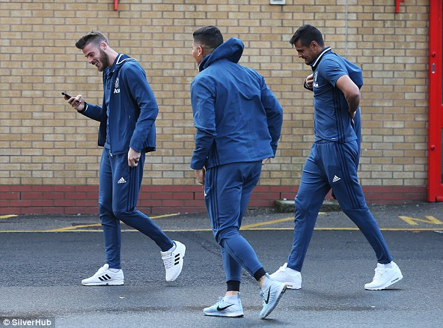 De Gea laughs while looking at his phone as he arrives at Old Trafford with his team-mates