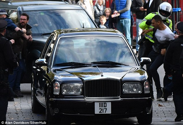 Fight back: Police grabbed two men trying to get near the limousine belonging to the controversial monarch
