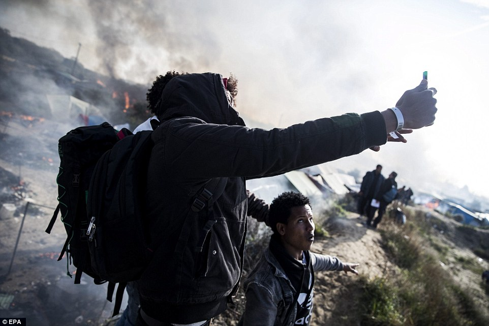 Migrants takes selfies of the burning camp that was once a make shift home to more than 7,000 migrants