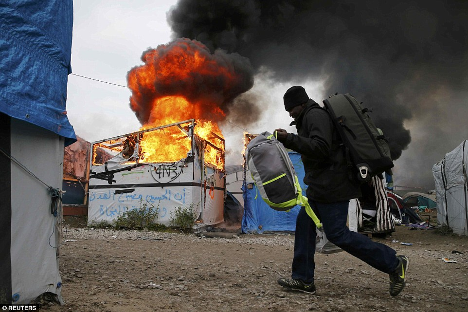 A migrant with his belongings walks past a burning makeshift shelter in the Jungle on the third day of their evacuation