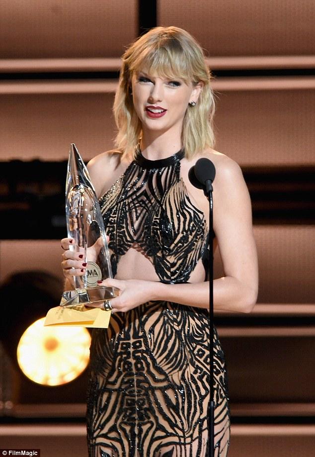 Olhos no prêmio: ela subiu ao palco para apresentar o prêmio principal na entrega de prémios - Entertainer of the Year