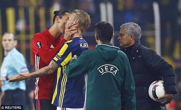Fenerbahce defender Kjaer has his arms by his side as Ibrahimovic shouts in defender's ear
