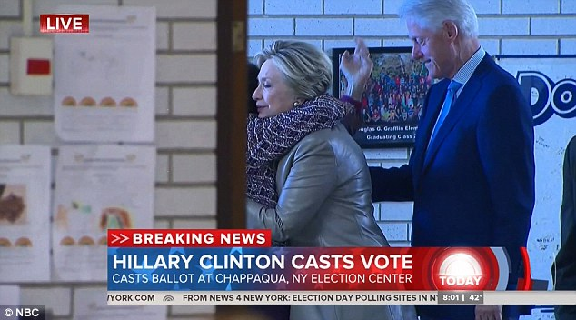 Hillary Clinton, sporting a leather jacket and with Bill Clinton at her side, hugs a fellow New York voter at her polling place this morning
