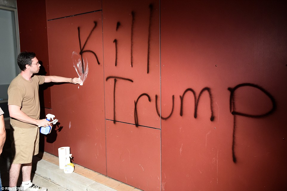 Oakland: A member of the public tries toscrub away 'Kill Trump' graffiti as demonstrators riot in California