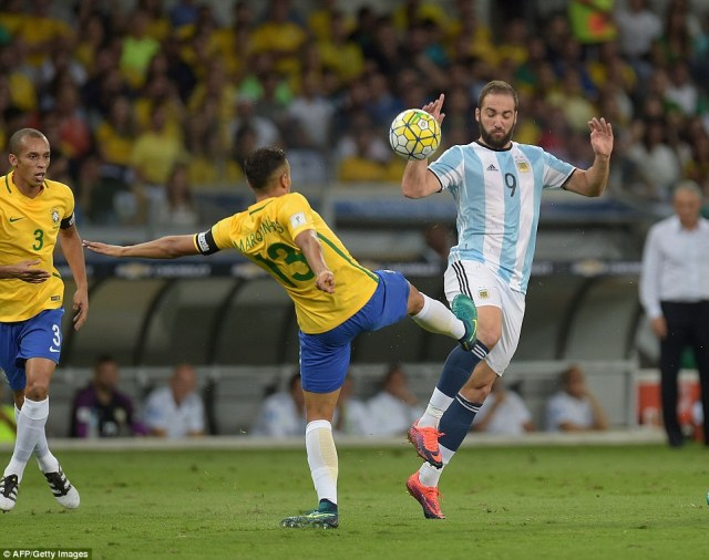 Marquinos leaves a foot in on Juventus striker Gonzalo Higuain as the two players battle for the ball in the centre of midfield