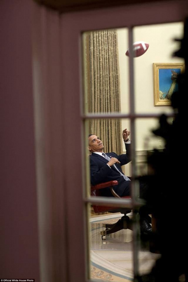 President Barack Obama plays with a football in the Oval Office on August 23, 2009