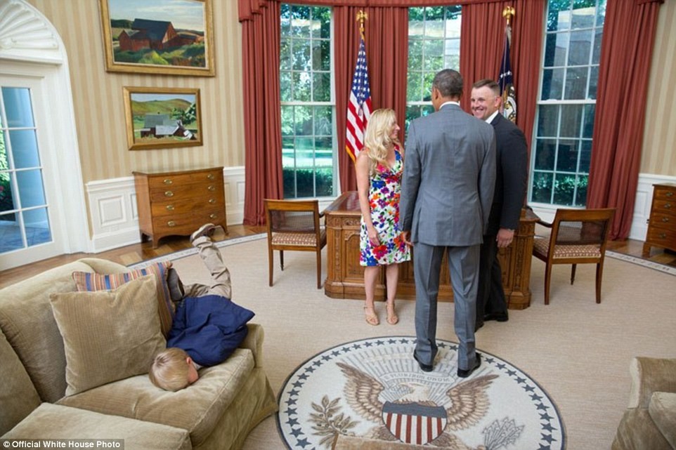 President Barack Obama visits with a departing United States Secret Service agent and his wife as their son dives into a couch in the Oval Office, June 23, 2014