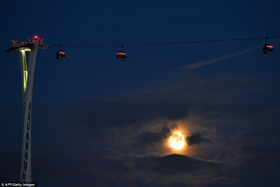 The supermoon can be seen here through the clouds behind the Emirates Air Line cable car, in London's Docklands