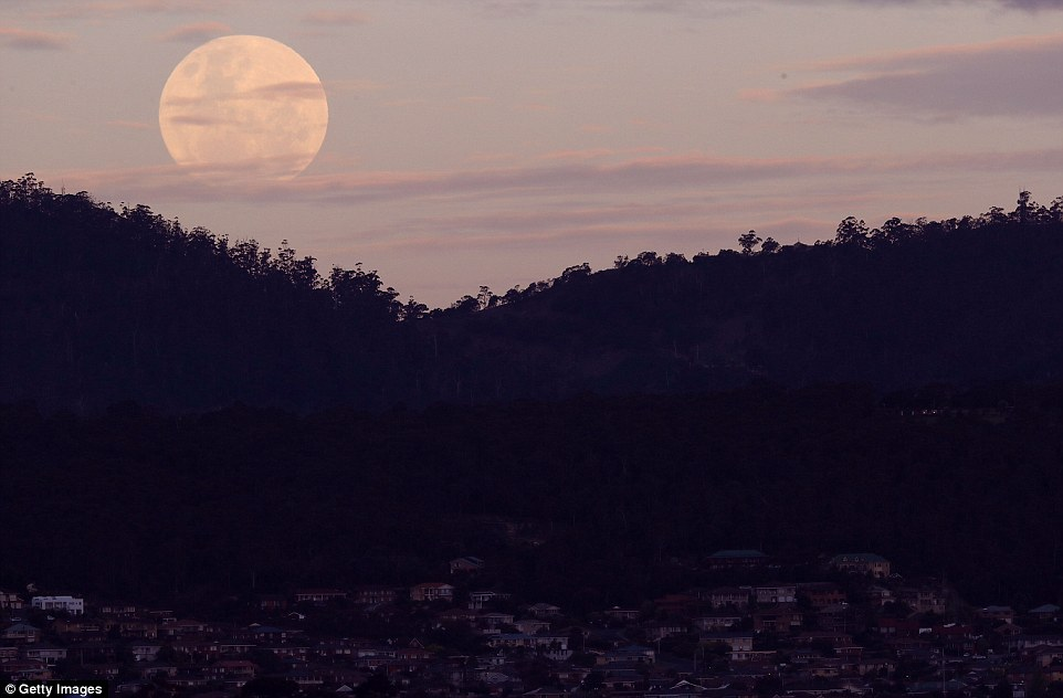 The supermoon can be seen captured above Hobart as the sun begins to disappear