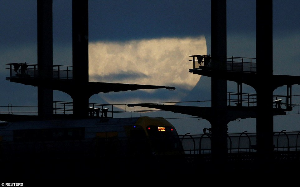 The grandeur of the supermoon shown behind a train on the Sydney Harbour Bridge on Monday night