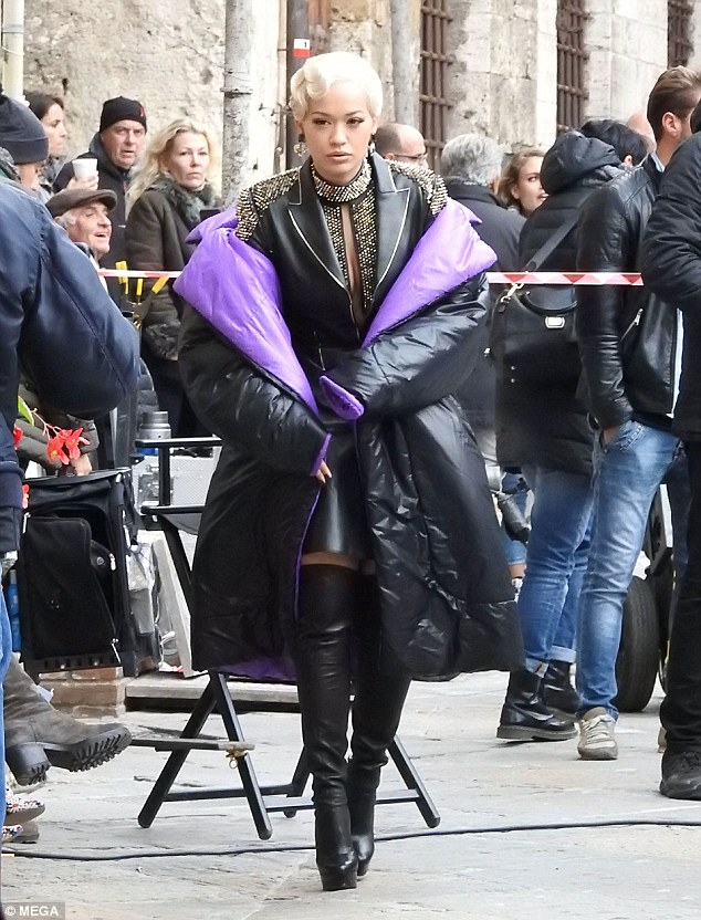 Keeping cosy: In-between takes, the songstress was warming up in a giant padded jacket with bright purple lining