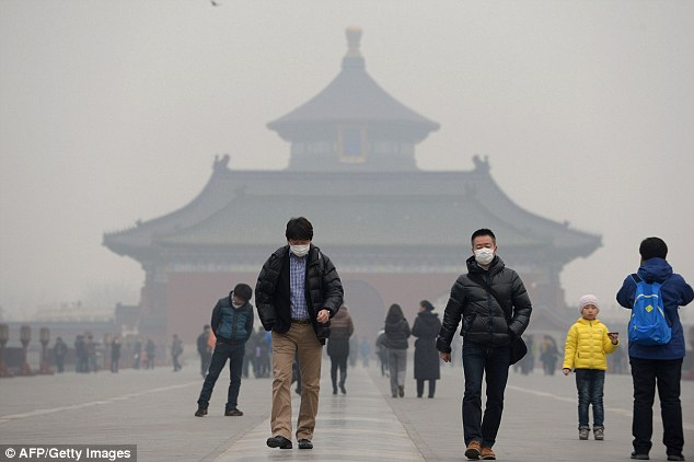 Tourists wearing masks in Temple of Heaven in haze-covered Beijing, China. Studies show pollution is causing the deaths of up to 500,000 people in the country a year.
