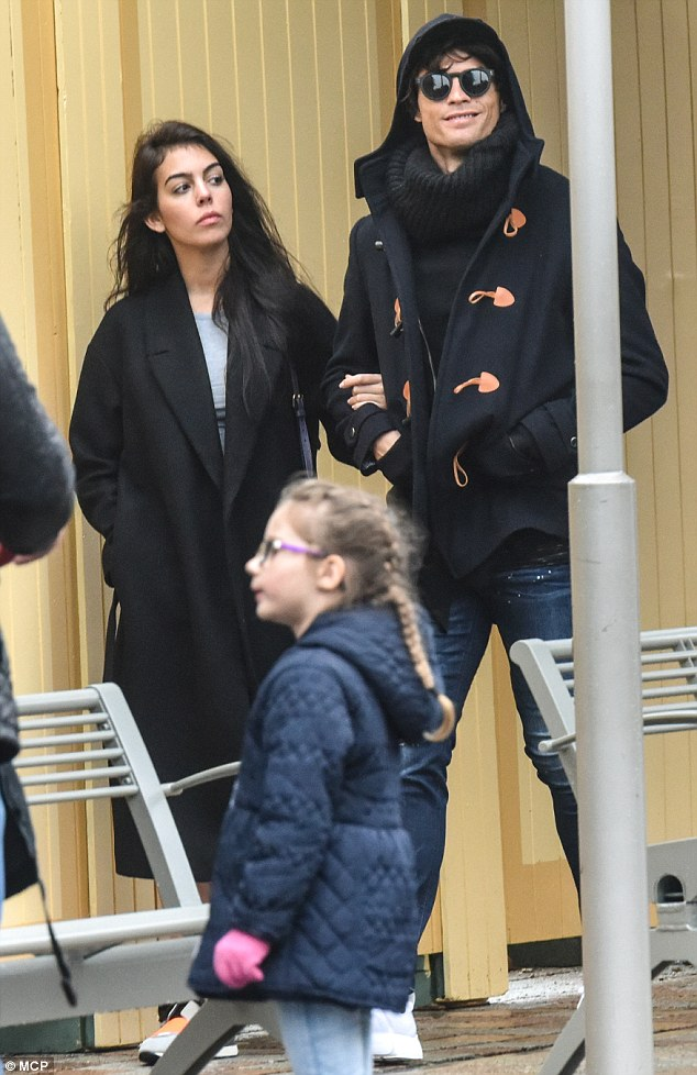 Soaking up the sights: The footballer offered a cheerful grin as he walked arm in arm with Georgina