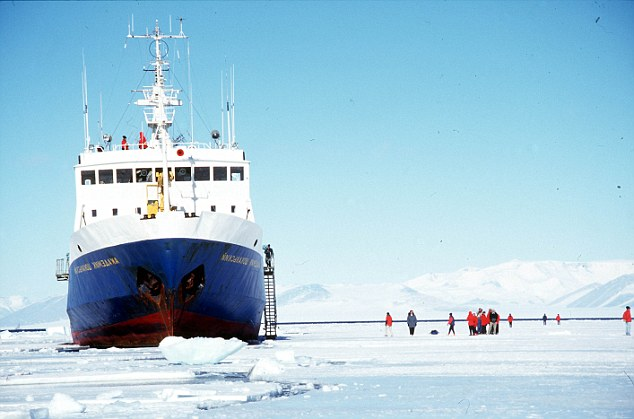 Passengers from the Russian ship 'Akademik Shokalskiy' explore the frozen Ross Sea in the Antarctic. Mount Erebus volcano is in the background