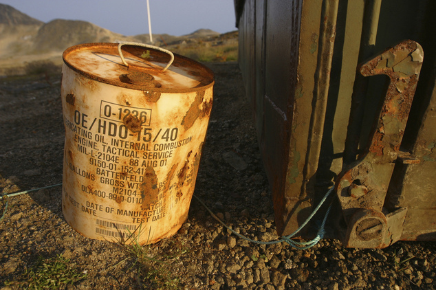 A rusty container of lubricant oil for a U.S. military vehicle stands among abandoned US military material in 2005