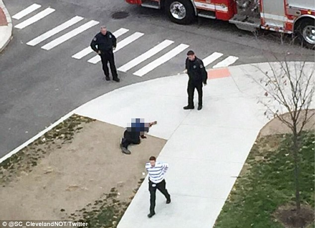 A knife-wielding man was killed on Monday after going on a rampage at the Ohio State University. Above, a body is seen on the campus