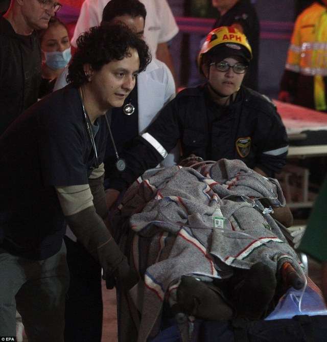 Medical staff from the San Juan de Dios hospital transfer 27-year-old Brazilian footballer Alan Ruschel after he as pulled alive from the wreckage of the crash