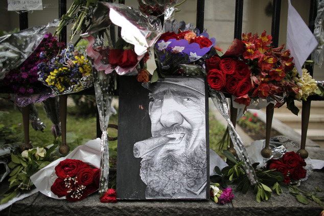 A caricature depicting Cuba's late leader Fidel Castro is surrounded by flowers at a makeshift memorial outside the Cuban embassy in Buenos Aires, Argentina,...