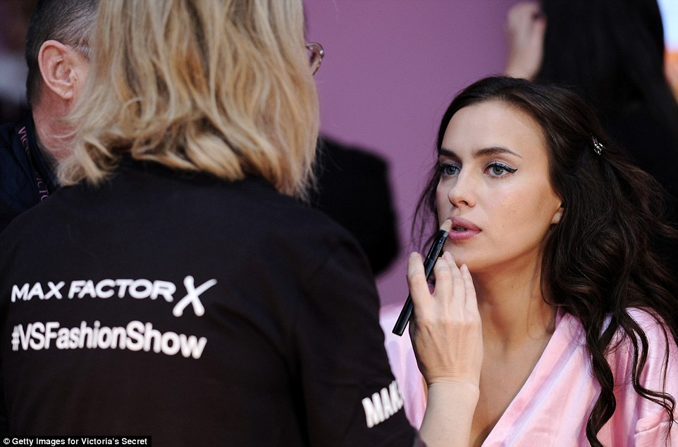 Lip service: The beauty sat patiently as her lips were painted a perfect deep pink ahead of the big show