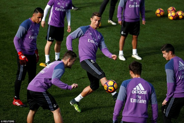 Cristiano Ronaldo controls the ball as he's surrounded by his Real Madrid team-mates during Friday's training session