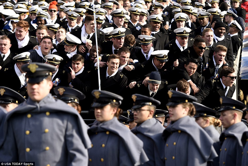 Navy Midshipmen yell at Army Black Knights cadets as the march onto the field