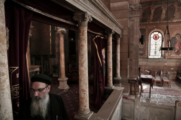 A Coptic clergyman examines the damages at the scene inside the St. Mark Cathedral in central Cairo, following yesterday's bombing