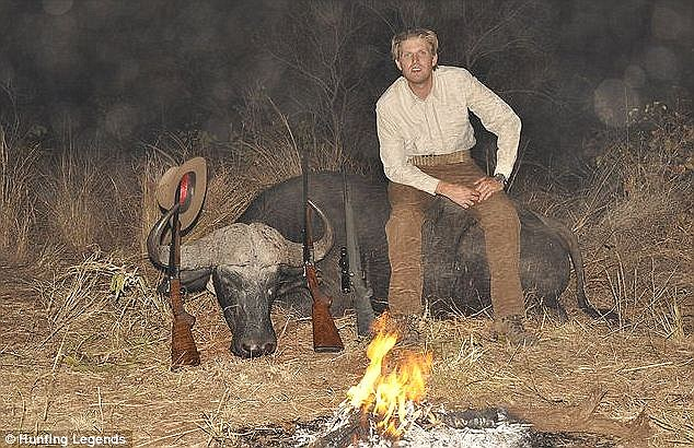 Eric Trump sits on top of a water buffalo in Zimbabwe, with three rifles and a hat propped up against the dead animal